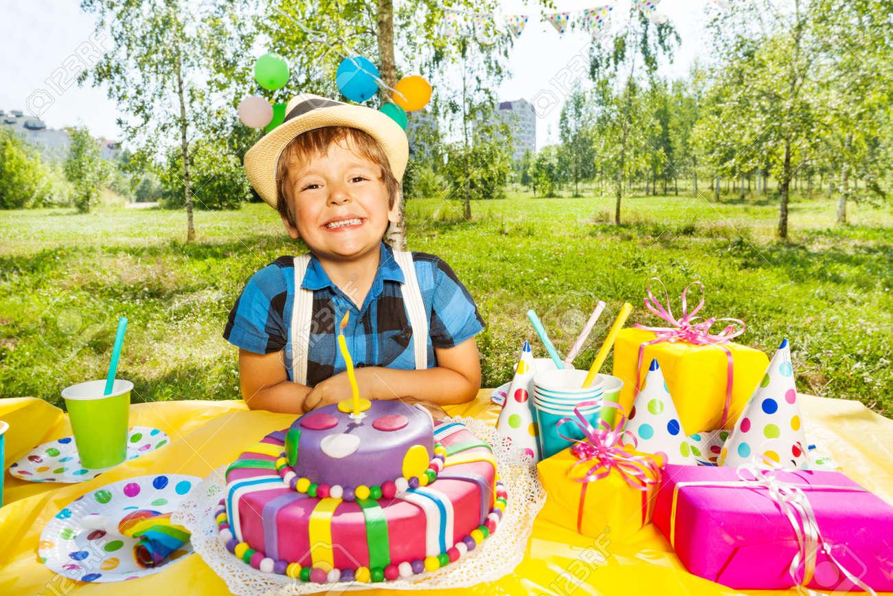 Portrait Of Happy Smiling Kid Boy Sitting Next To The Birthday