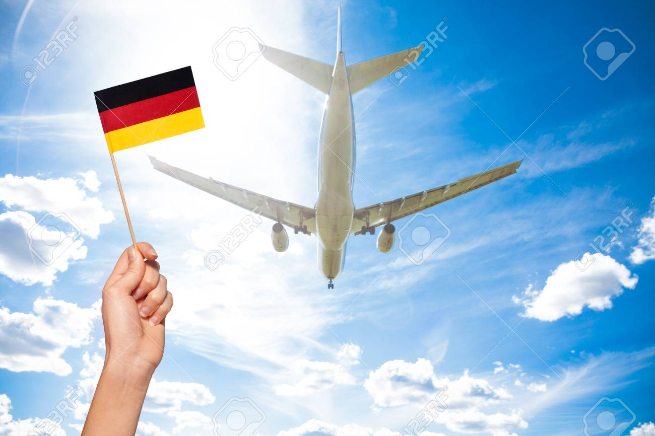 german flag against airplane flying through sky stock photo picture