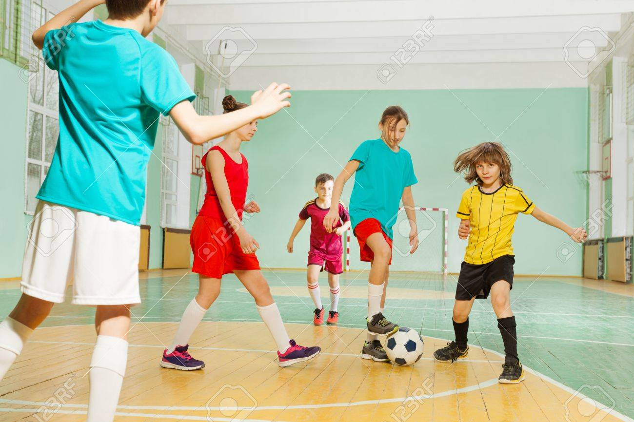 Children playing football in school sports hall - 81339925