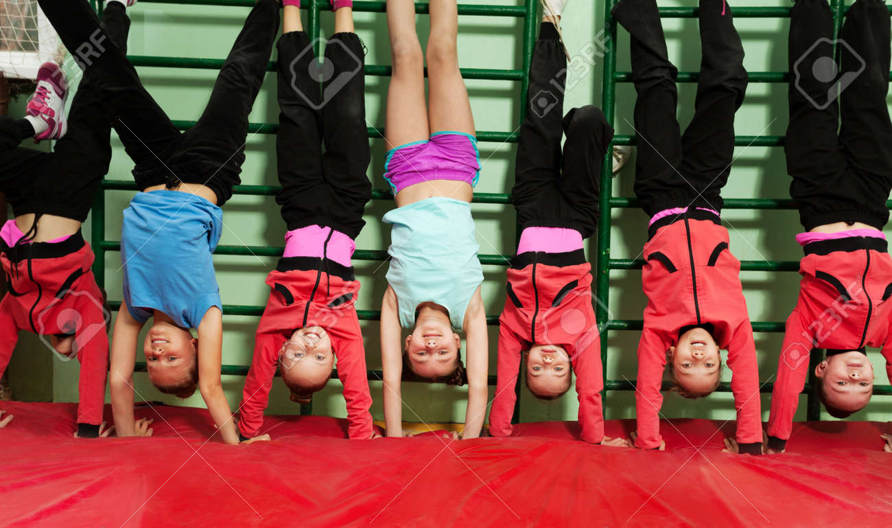 Sporty kids making handstand position in gym - 81312120