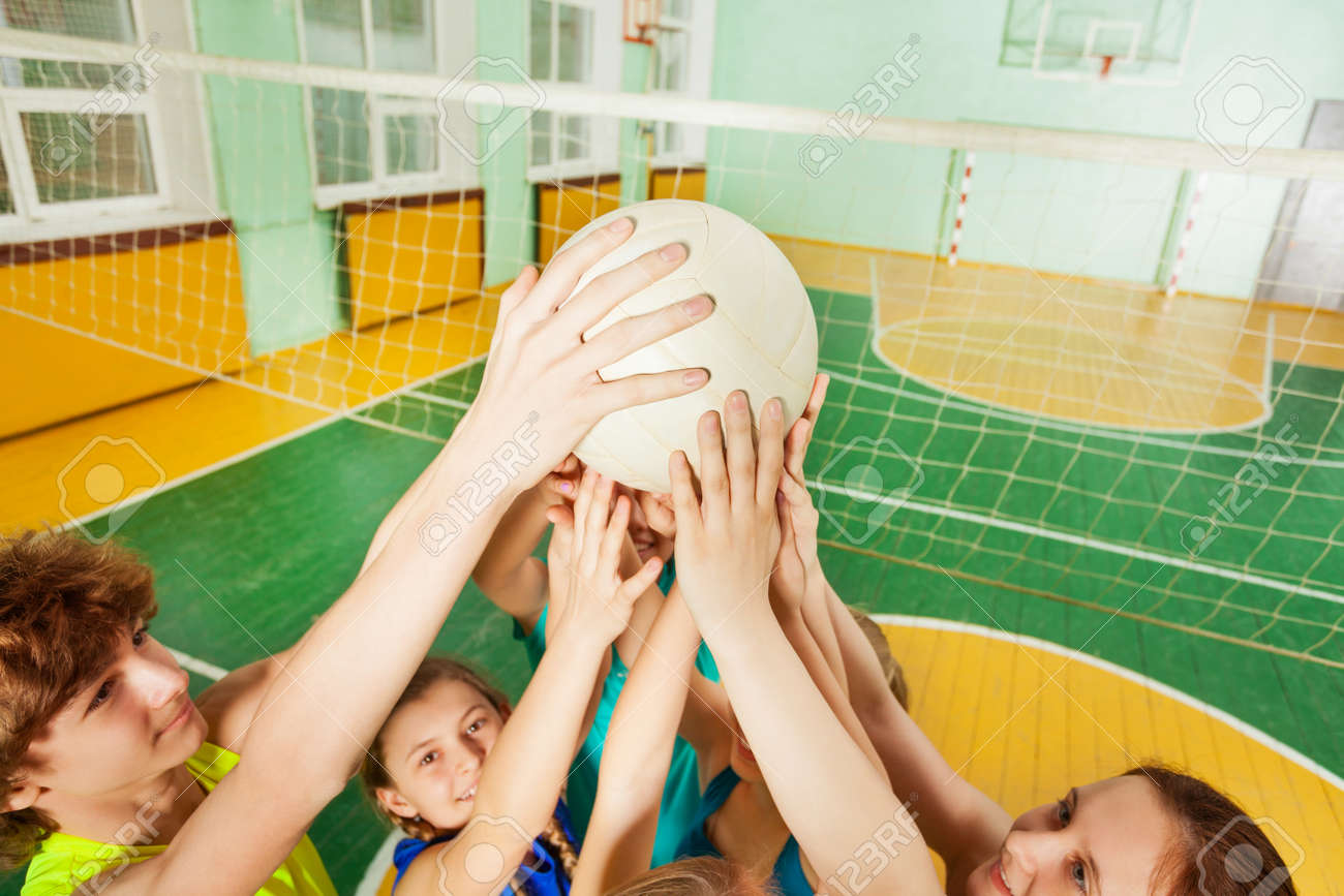 Teenage volleyball team players serving a ball - 82009996