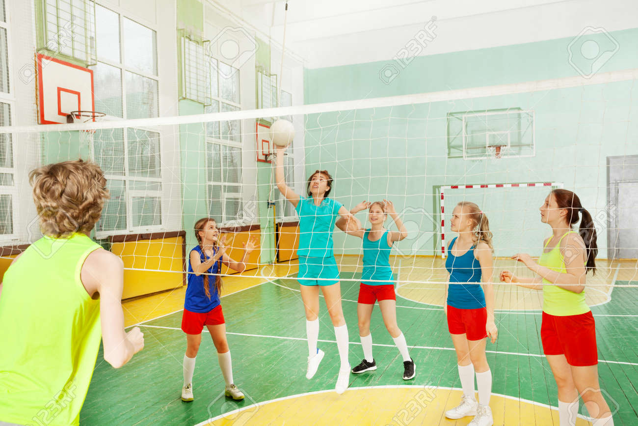Teen girl serving the ball during volleyball match - 81976062