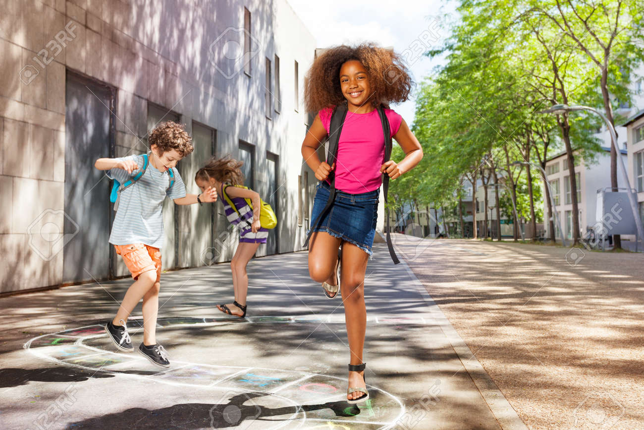 Curly girl with friends jumping hopscotch - 83421823