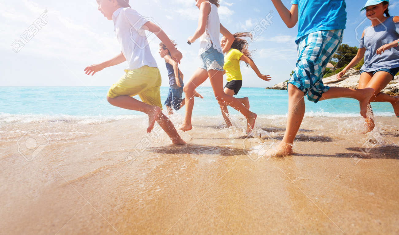 Close-up of running kids legs in shallow sea water - 87545891