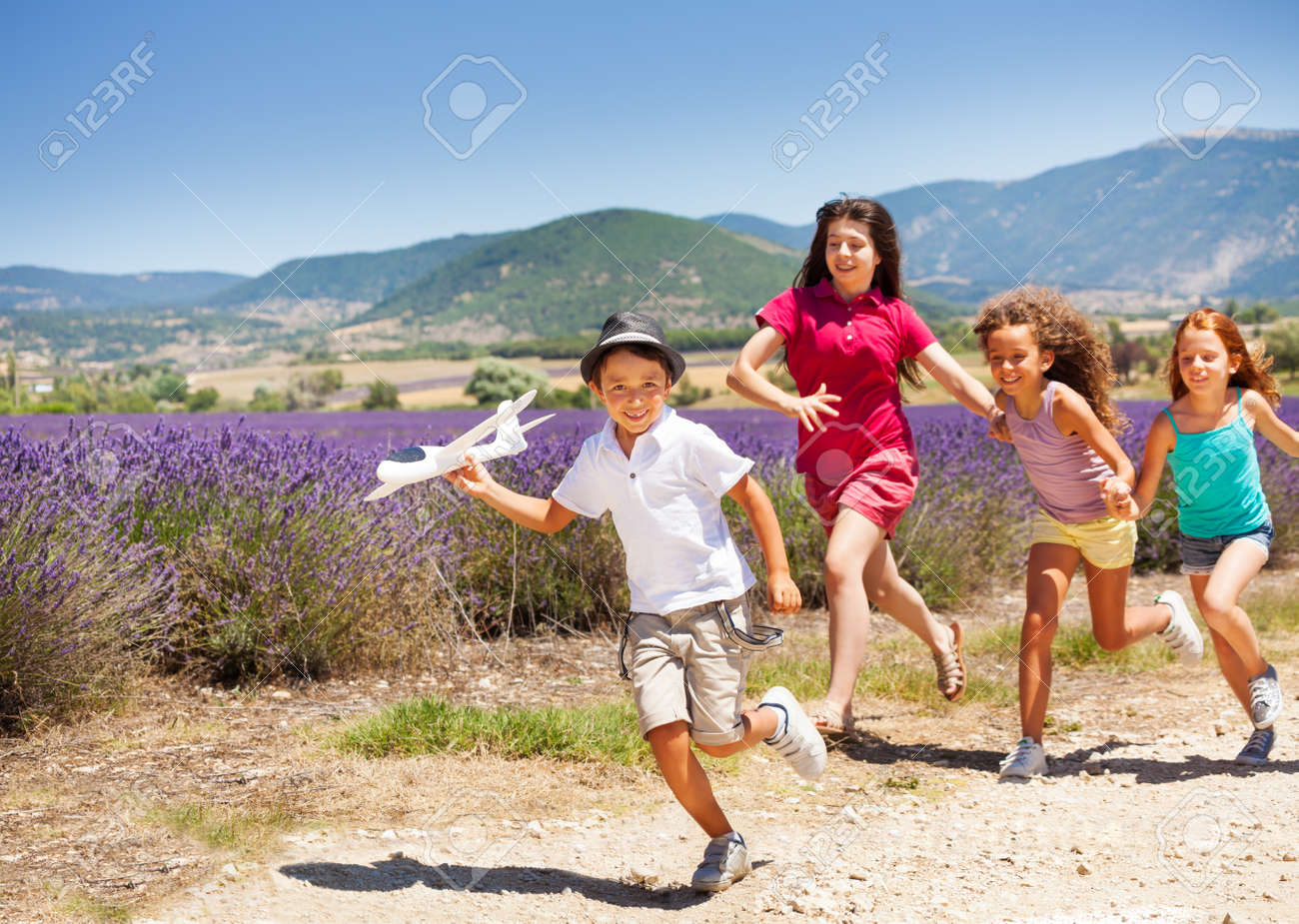 Three girls hurry after boy holding toy plane - 87407763