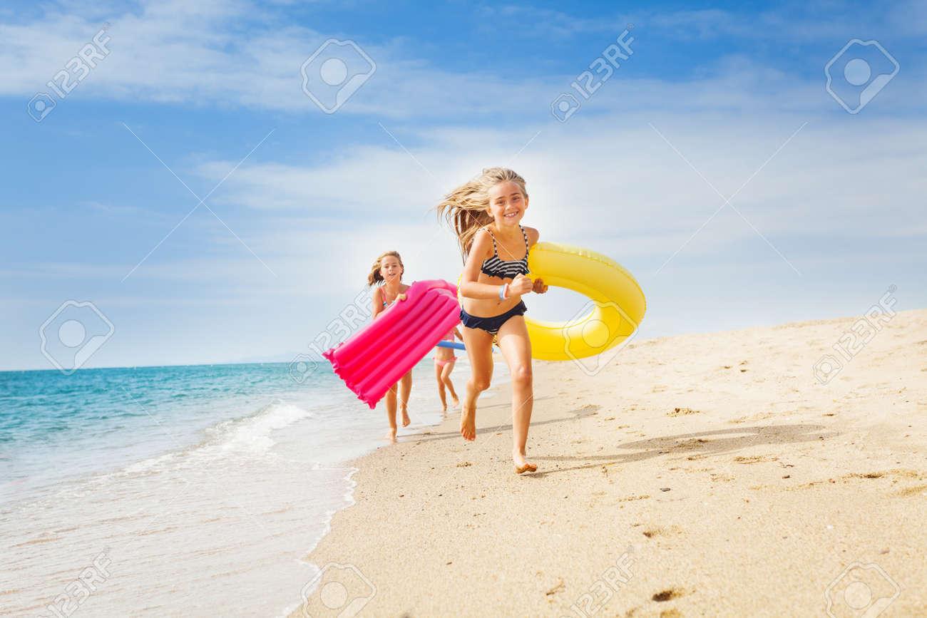 Happy kids having a race on sunny beach in summer - 88776215