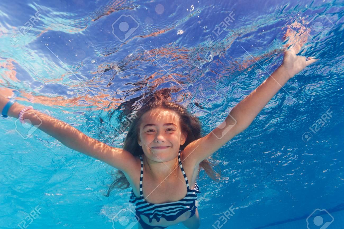 Beautiful preteen girl enjoying swimming under water of the pool - 106037073