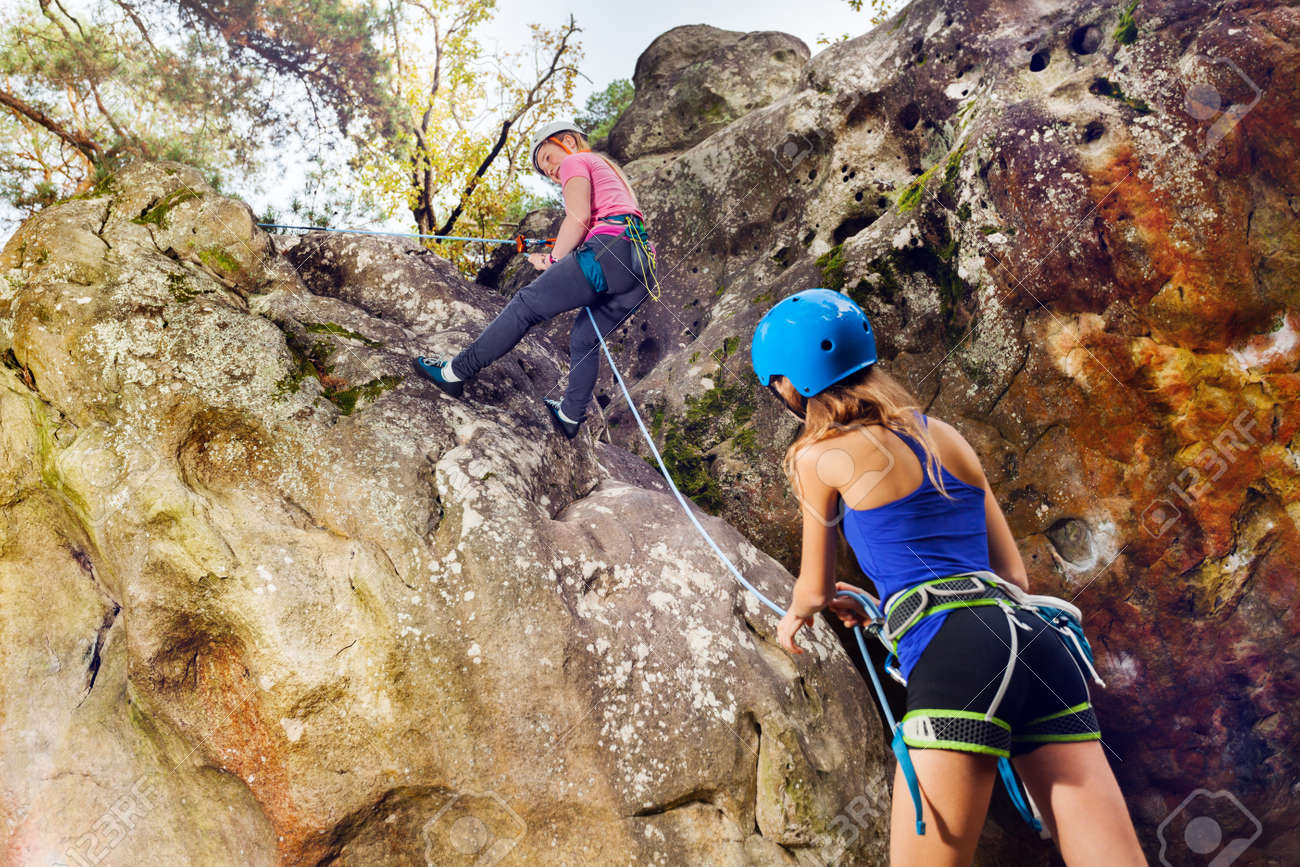 Female rock climbing instructor helping teenage girl to reach the summit of the mountain - 93312368