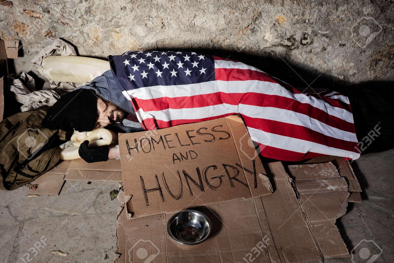 Man with alms bowl sleeping under American flag - 115373253