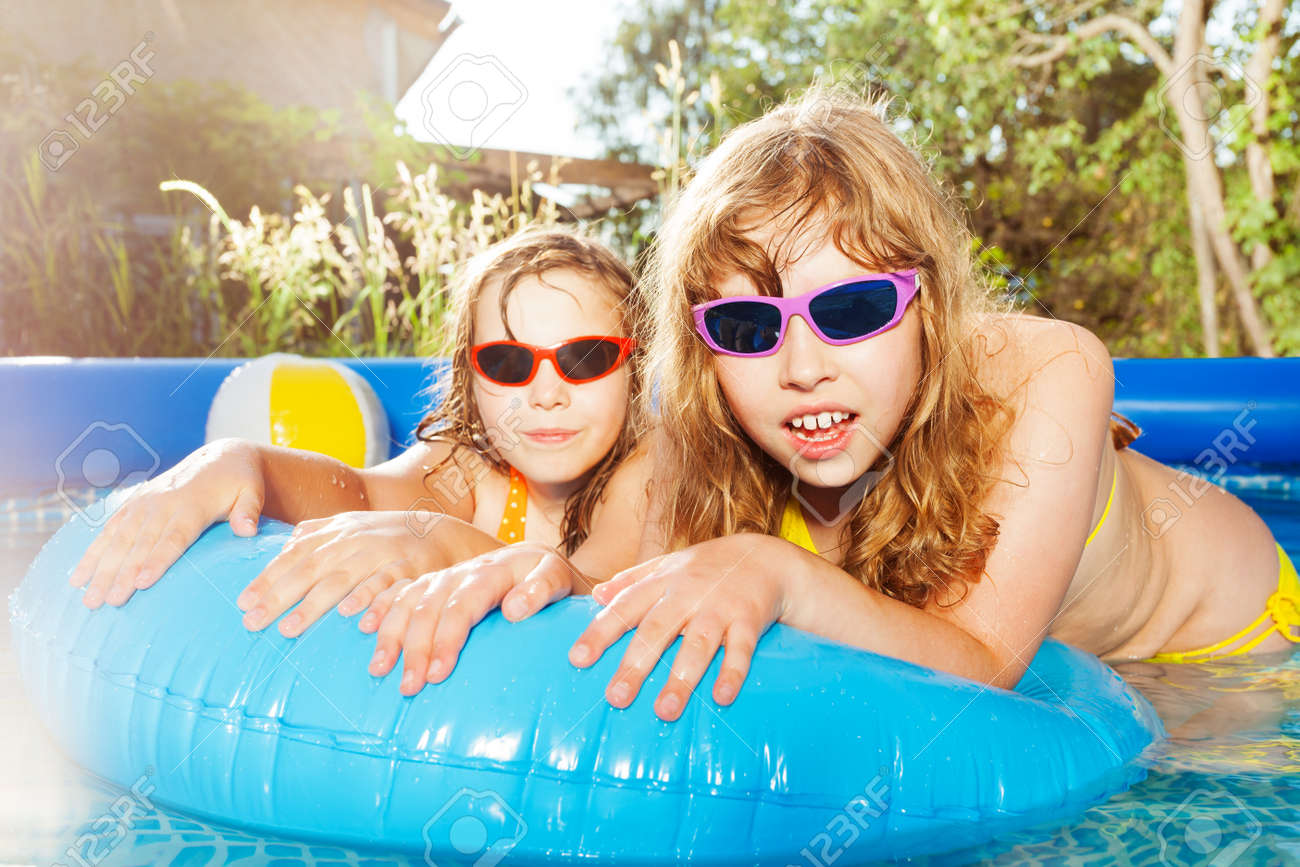 Two girls swimming in the pool with rubber ring - 120595459