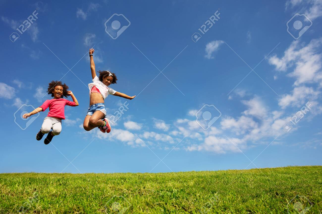 Two happy girls jump high over blue sky on lawn - 129575108