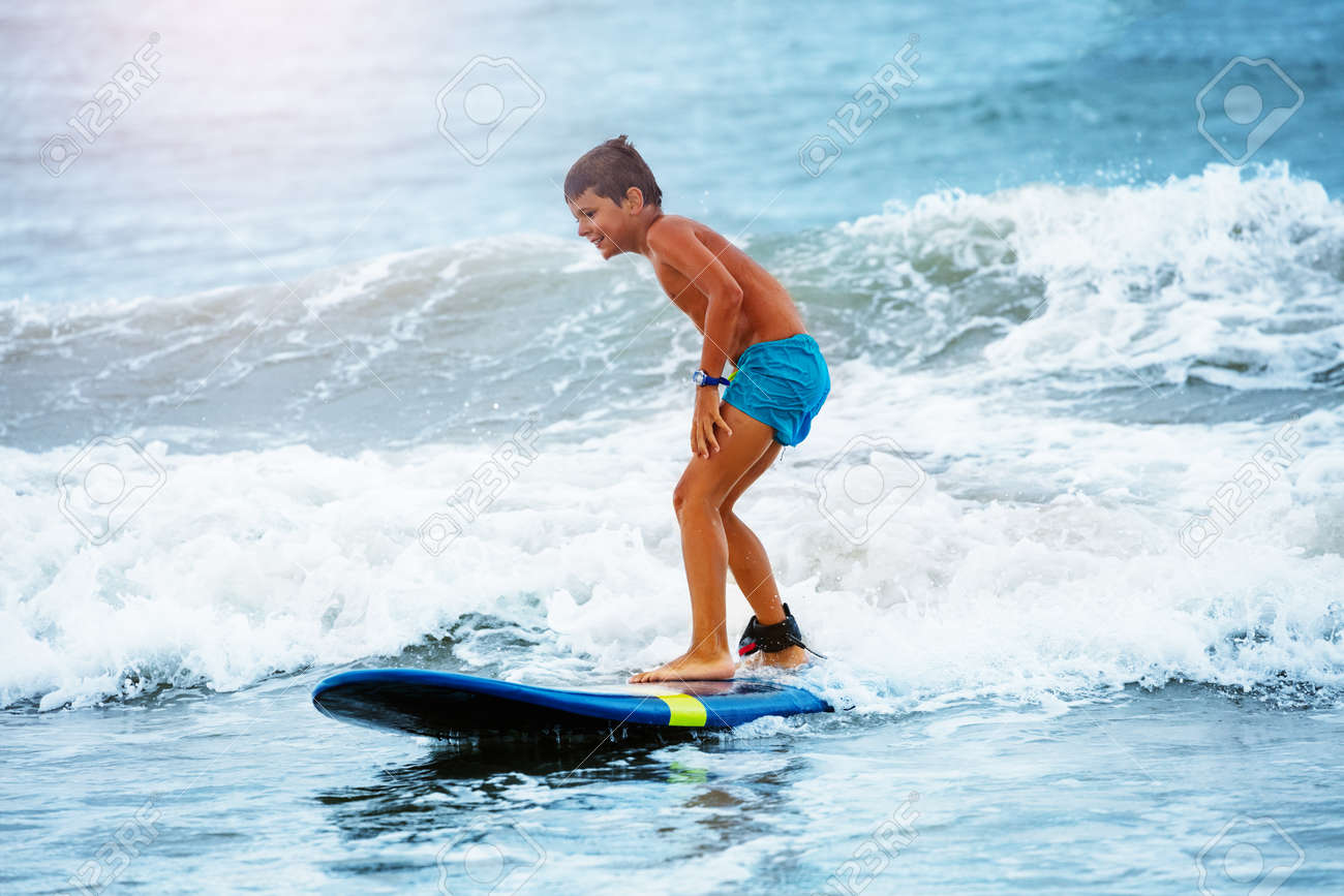 Little boy stand on the surfboard learn to ride - 135947087