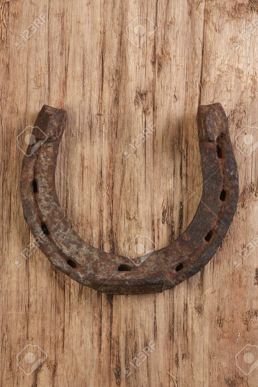 old rusty horseshoe on a wood background Stock Photo - 11254850