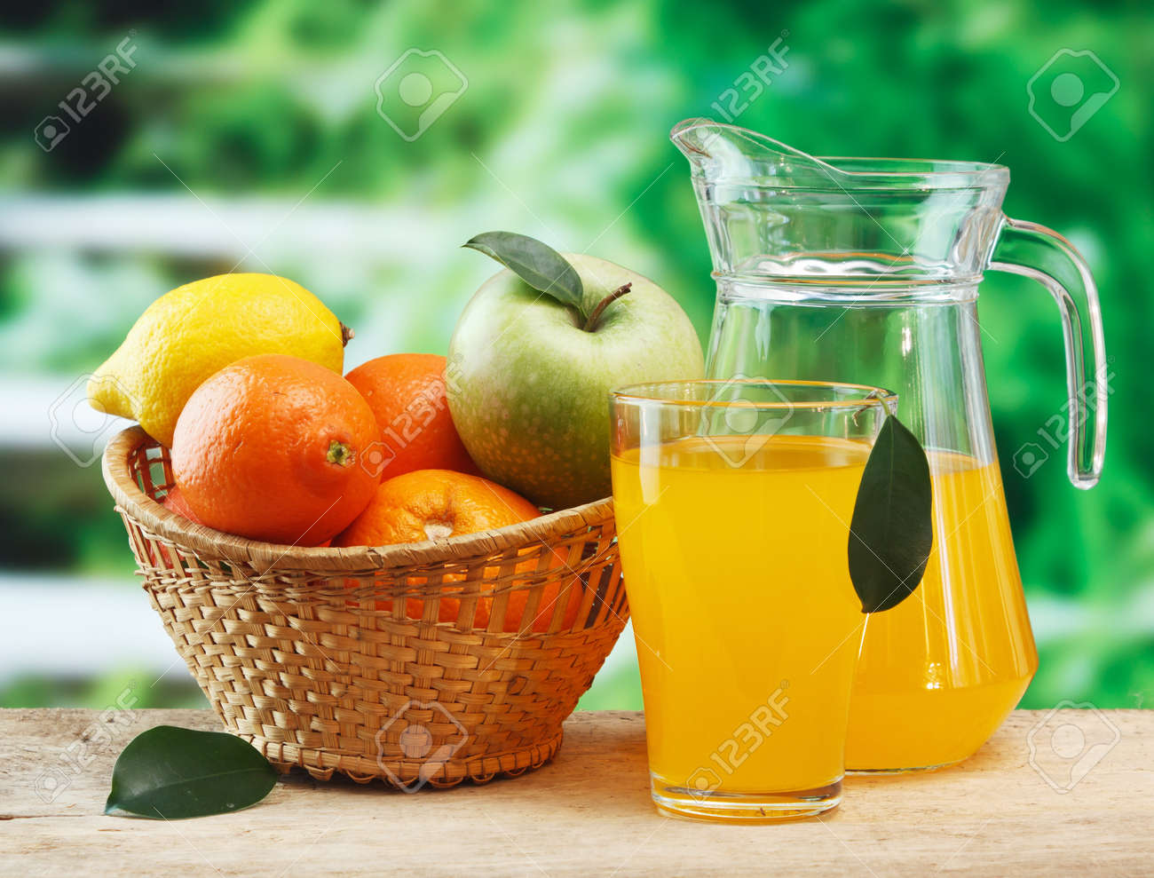 variety of fruit and juice on a wooden table in the garden - 15229454