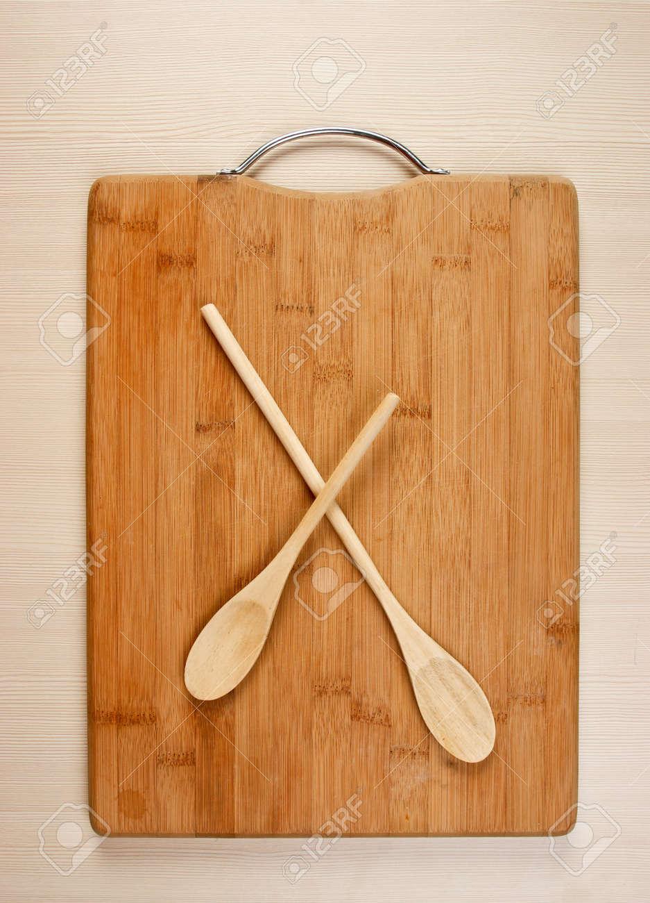 Cucchiaio di legno sul tagliere da cucina di bambù