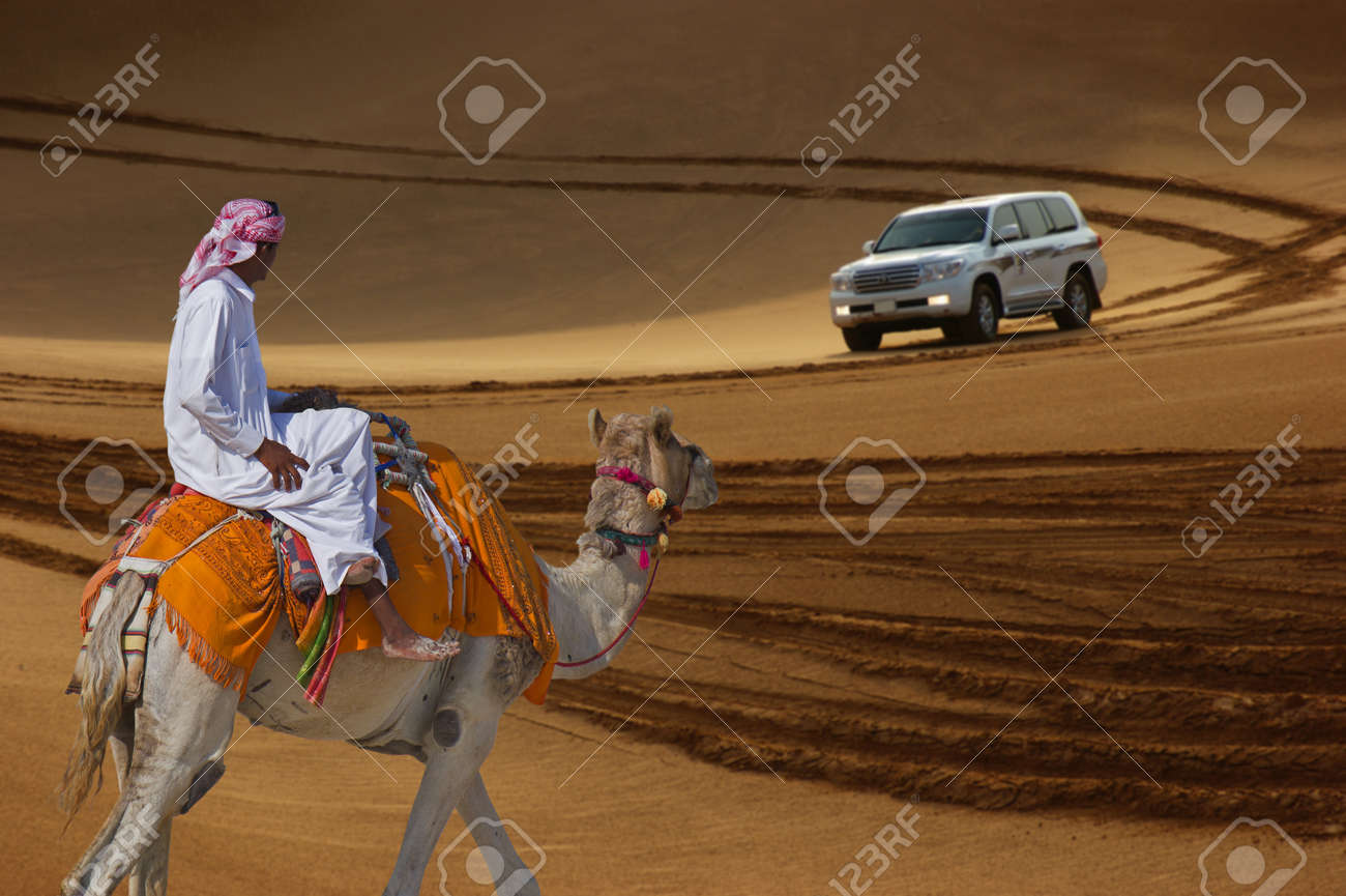 Bedouin on a camel in the desert and Jeep safari in the sand dunes - 17126130