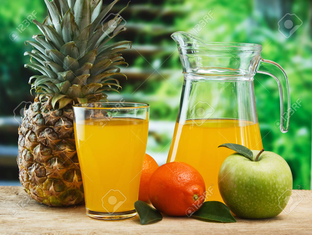 variety of fruit and juice on a wooden table in the garden - 18939852