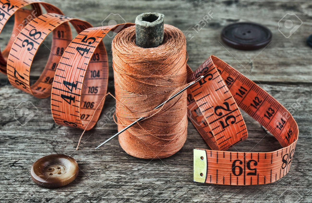 still life of spools of thread on a wooden background - 18923110