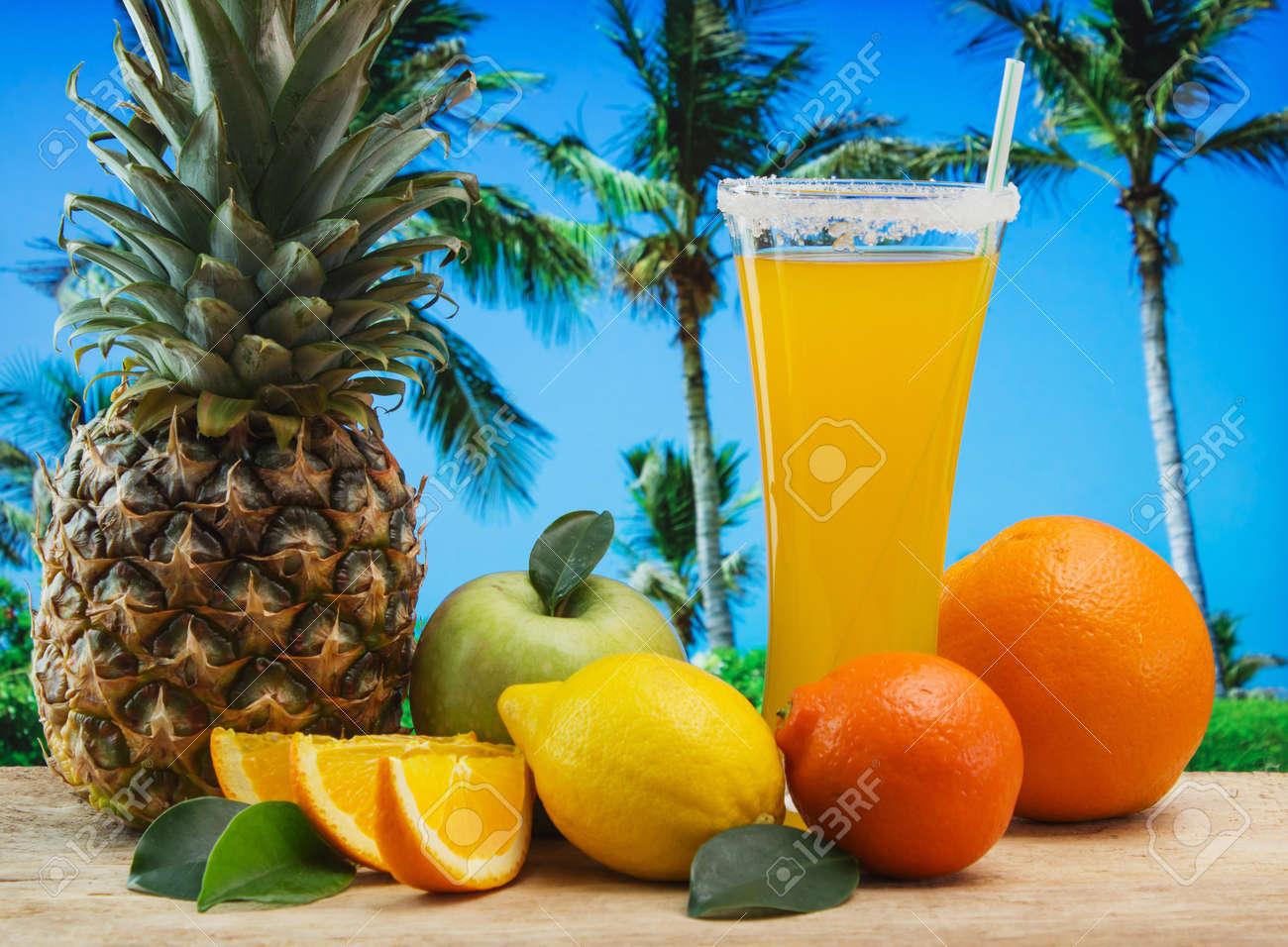 Glass of orange juice on a beach table - 18920564