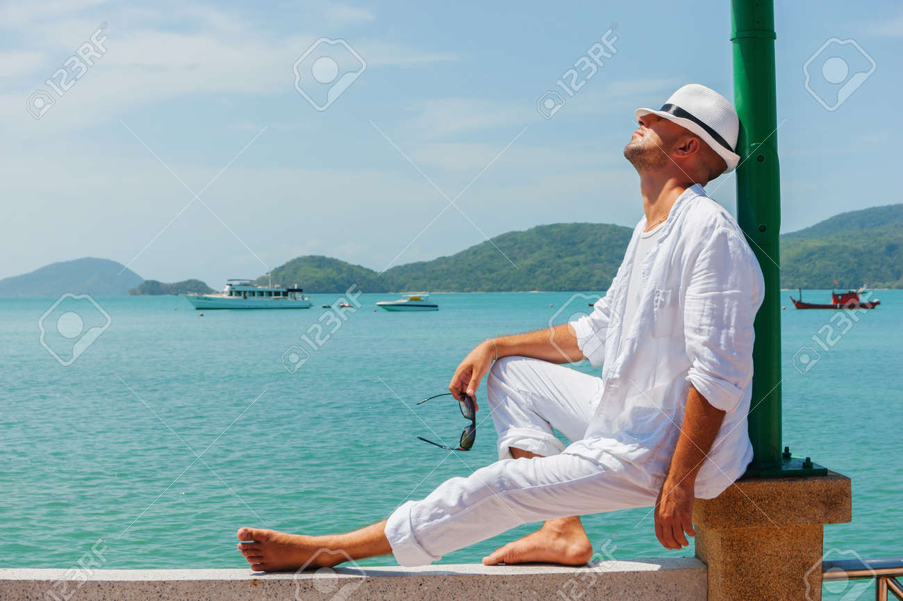 A young man in a white suit sits on the waterfront - 19555595