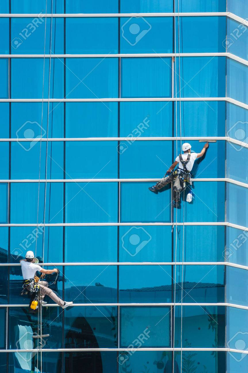 workers washing windows of the modern skyscraper building - 24775817