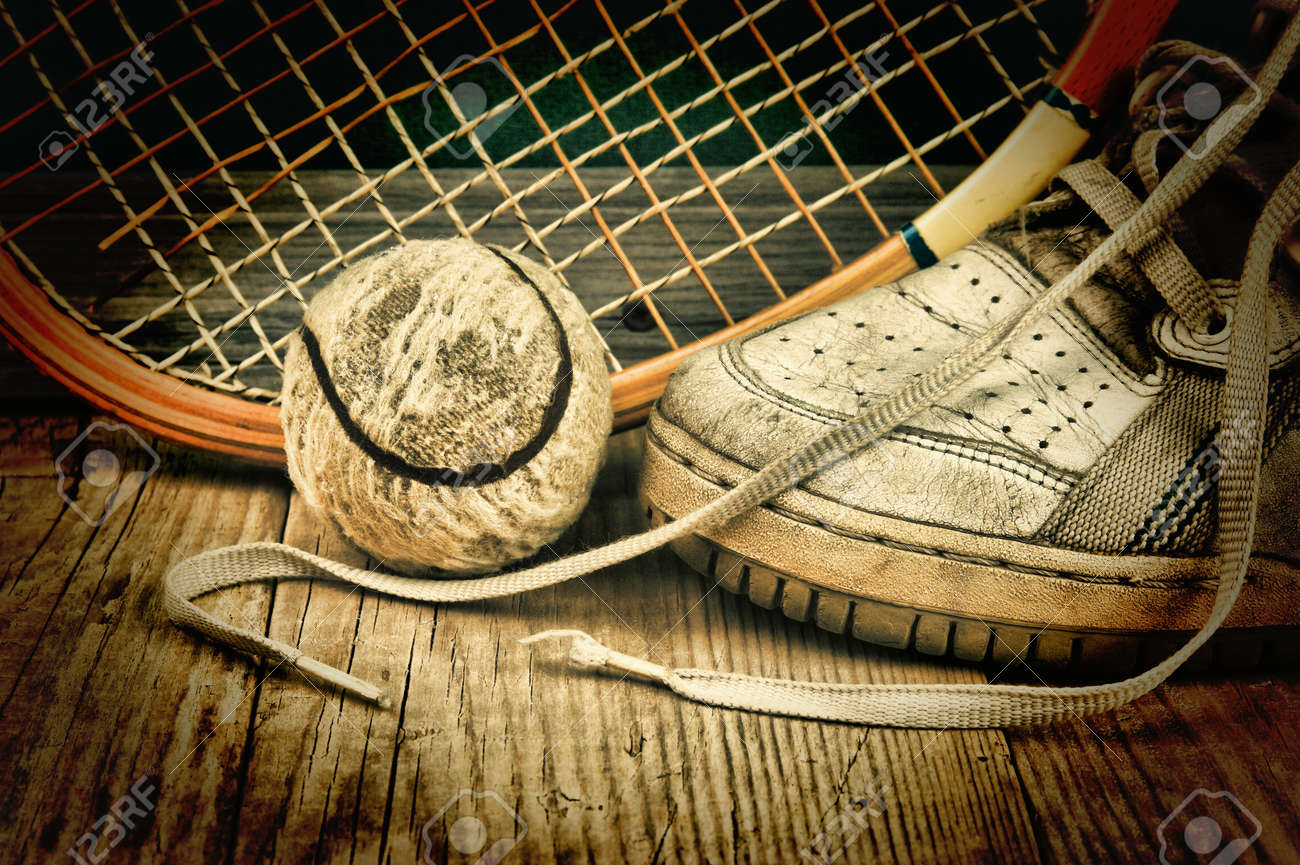 old tennis ball and racket with sneakers on a wooden floor - 29783623