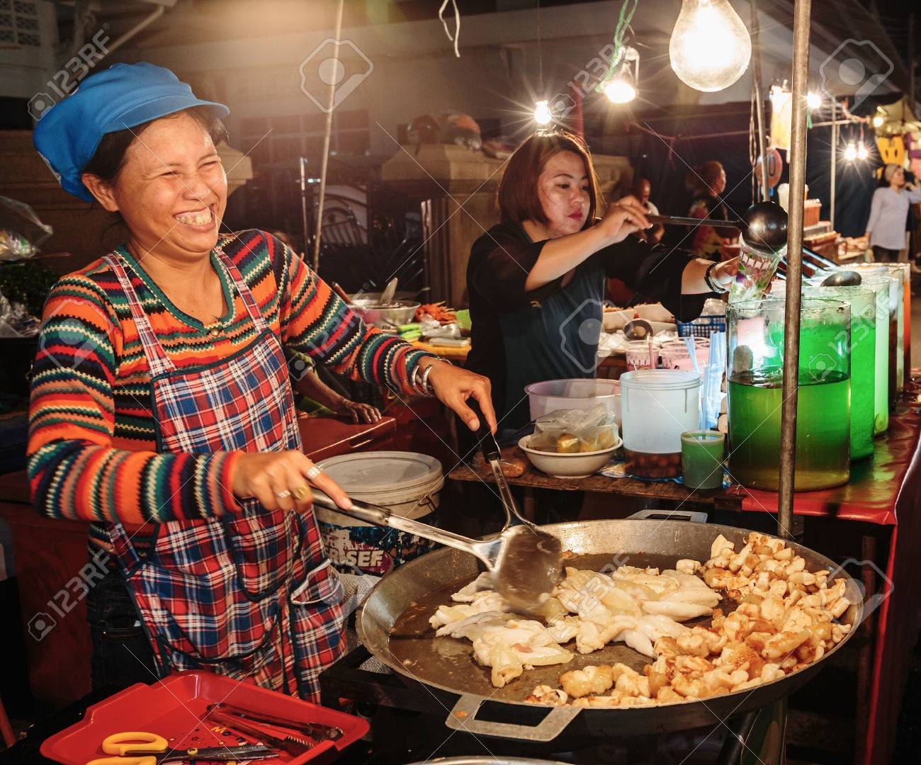 PATTAYA, THAILAND - APRIL 4, 2015: Woman in a street cafe fry food and smiling - 38893495