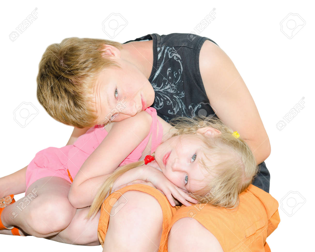 Two kids brother and sister curled up together isolated on white Stock Photo - 24058316