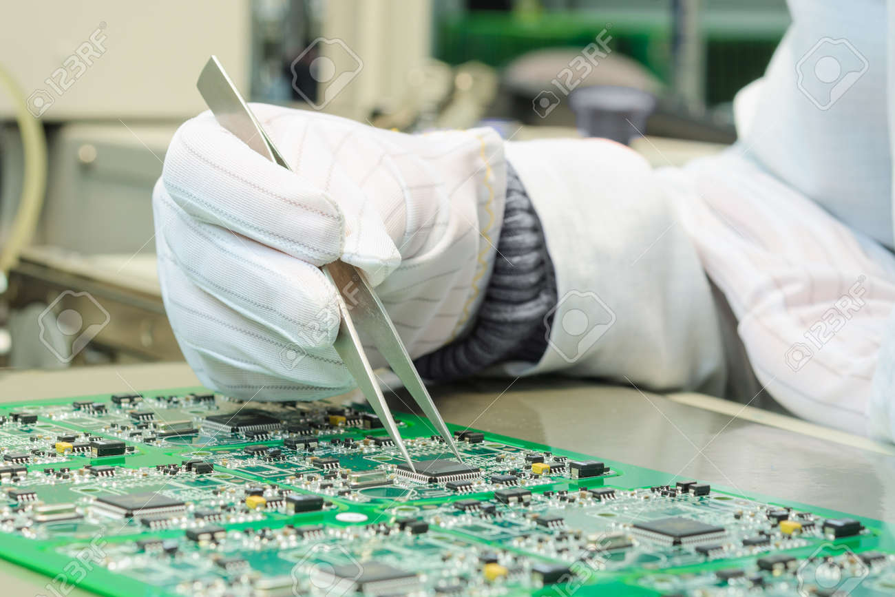 Quality control and assembly of SMT printed components on circuit board in QC lab of PCB manufacturing high-tech factory - 52412669