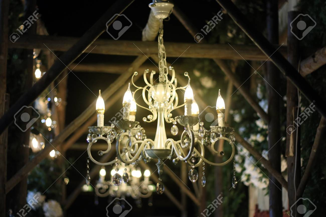 Crystal chandelier shines hanging on wood structure in the garden