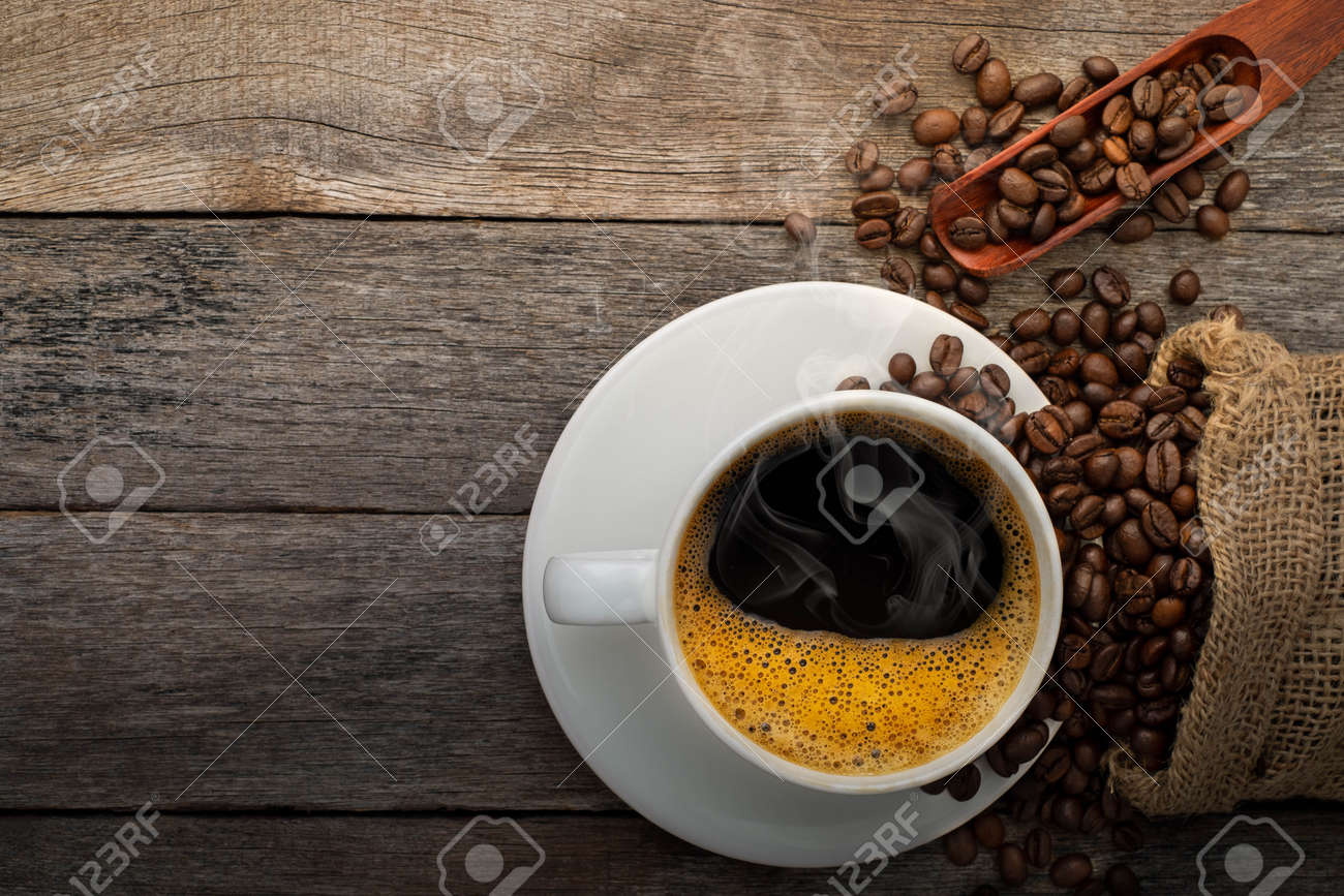 Top view above of Black hot fresh coffee with smoke and milk foam in a white ceramic cup with coffee beans roasted in burlap sack bag on wooden table background. Flat lay with copy space. - 149931843