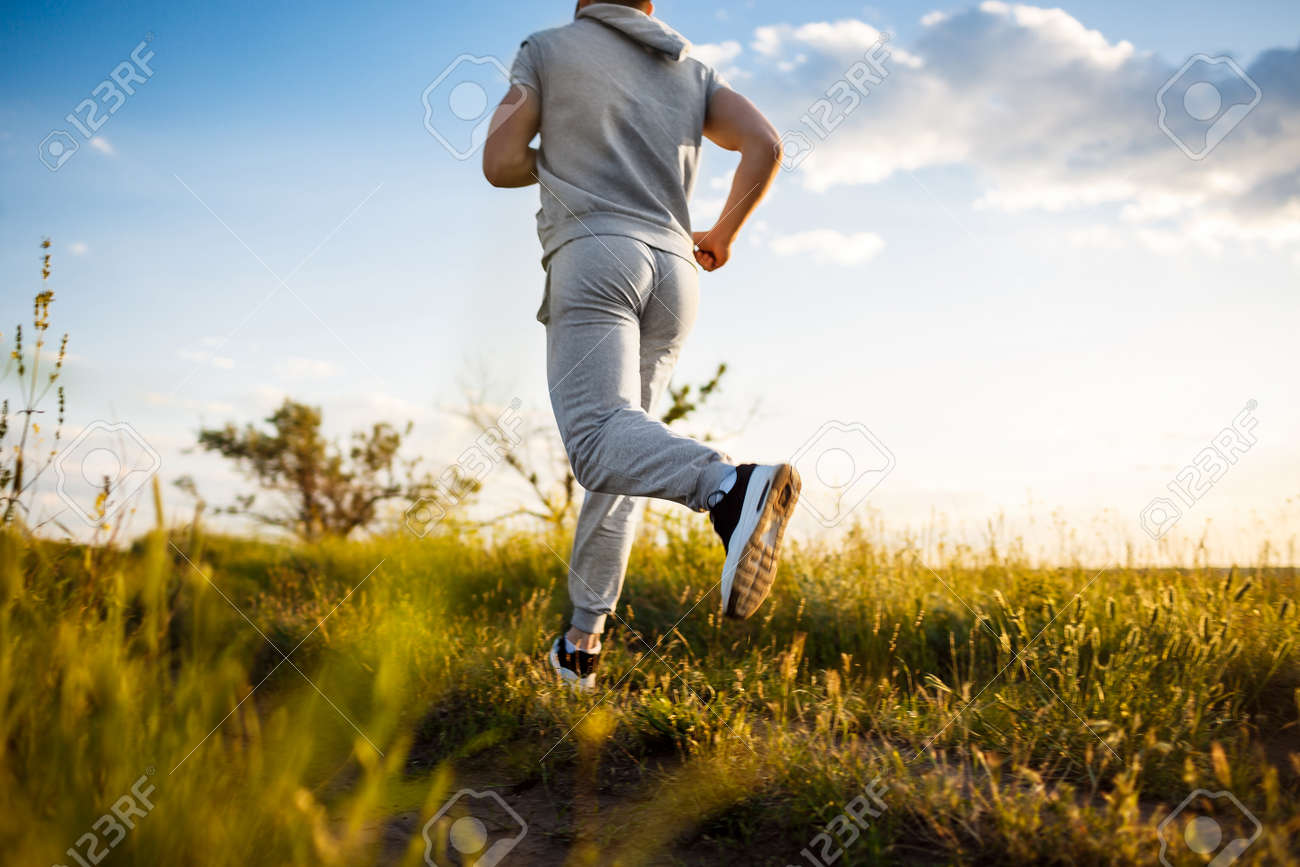 d534f94a5288 Close up photo of young sportive man jogging in field at sunrise. Stock  Photo -