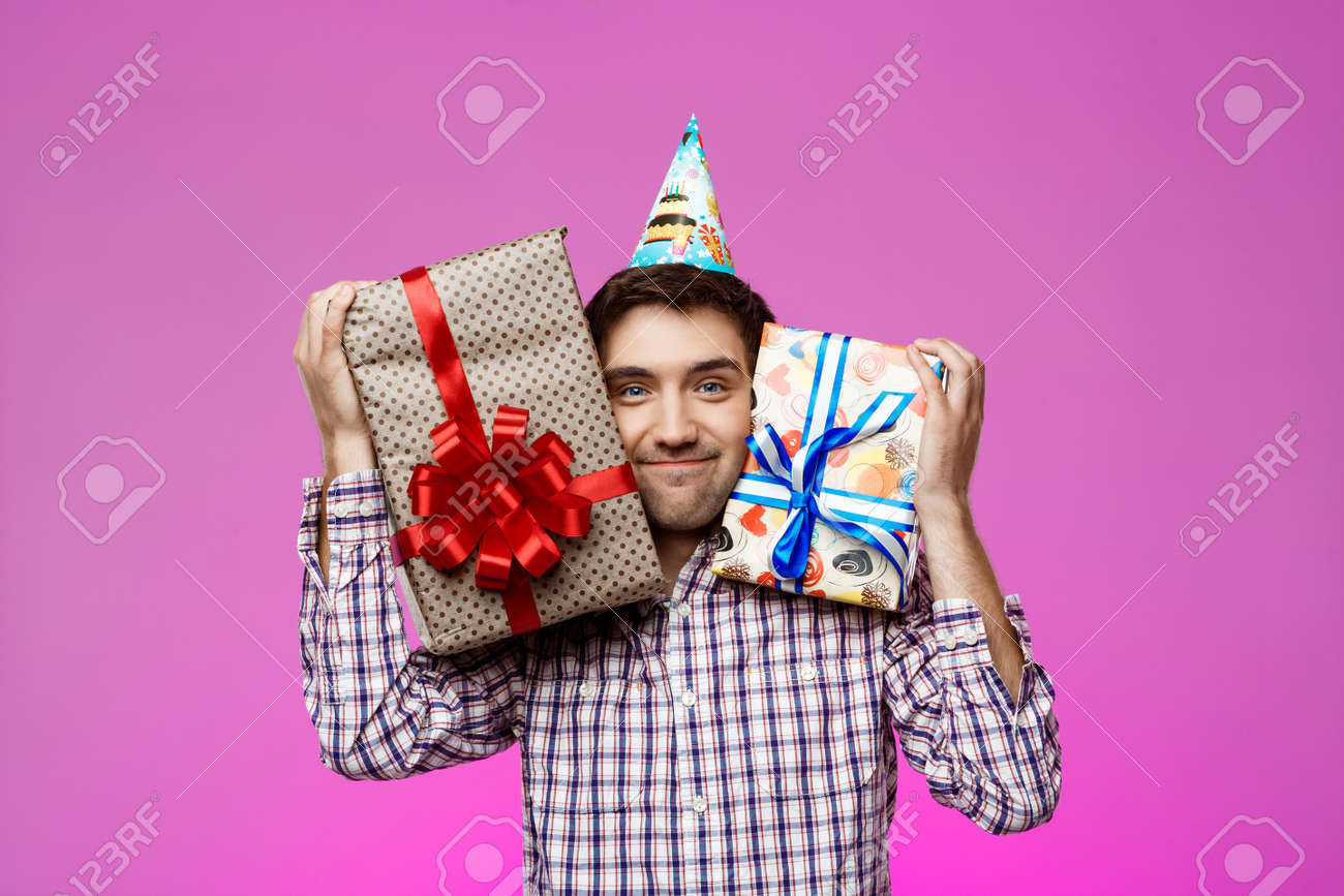 Happy Young Man Holding Birthday Gifts In Boxes Over Purple Background Copy Space Stock