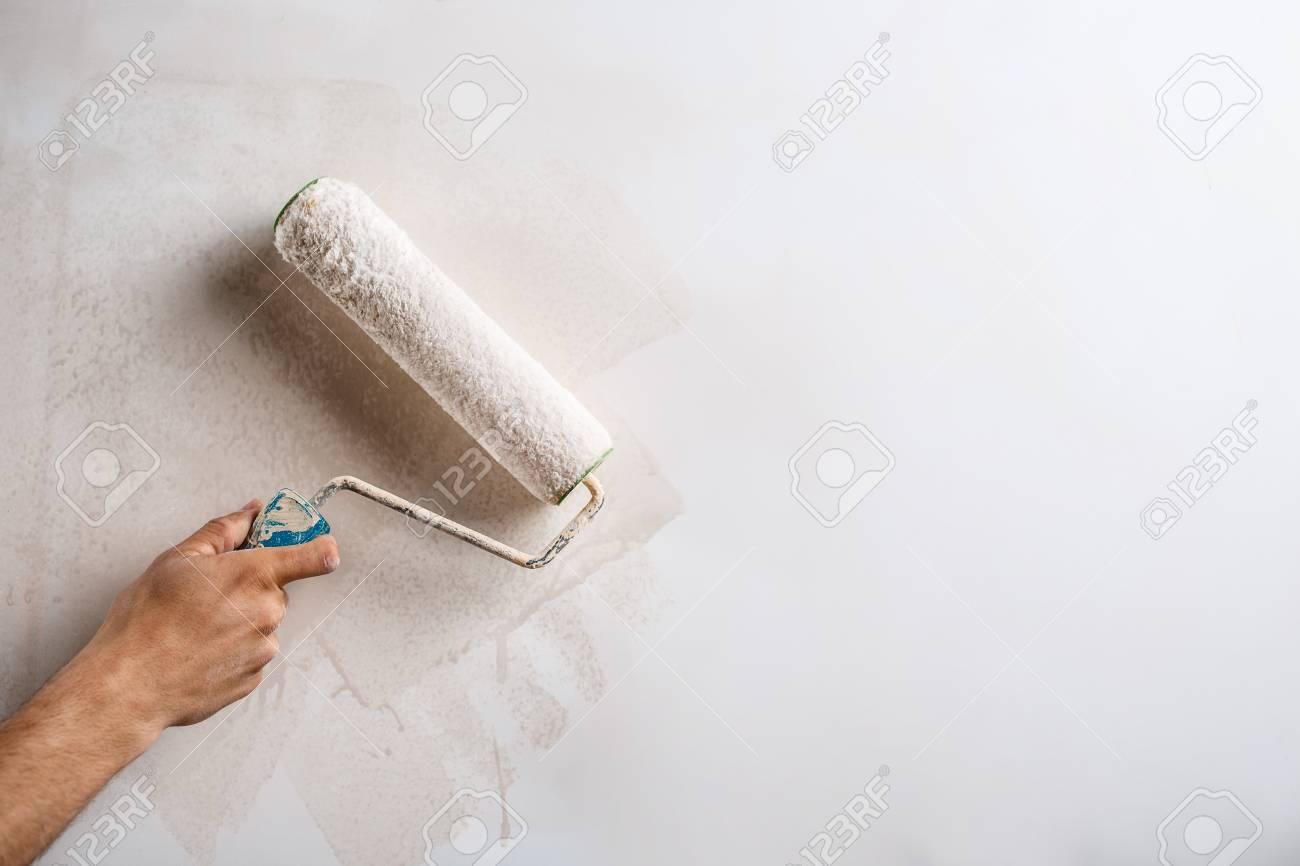 ローラーとハンド塗装壁のクローズ アップ。領域をコピーします。 の ...