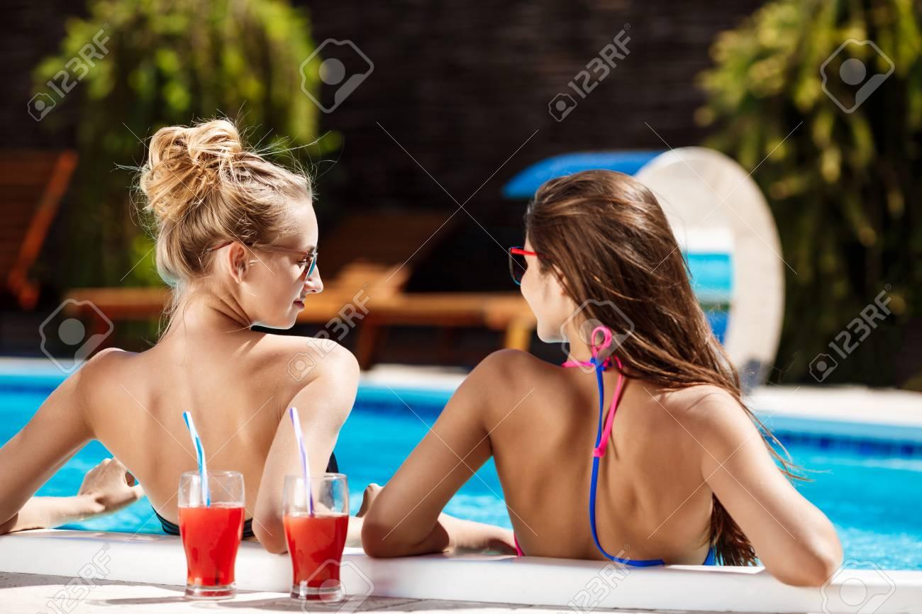 dbc2ebddf37b Jóvenes hermosas chicas en traje de baño sonriendo, hablando, relajarse en  la piscina. Copia espacio