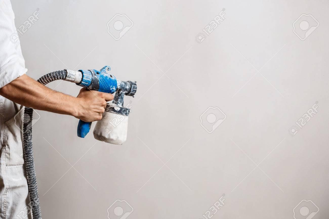 Mur De Peinture De Travailleur Avec Pistolet Pulvérisateur En Couleur Blanche