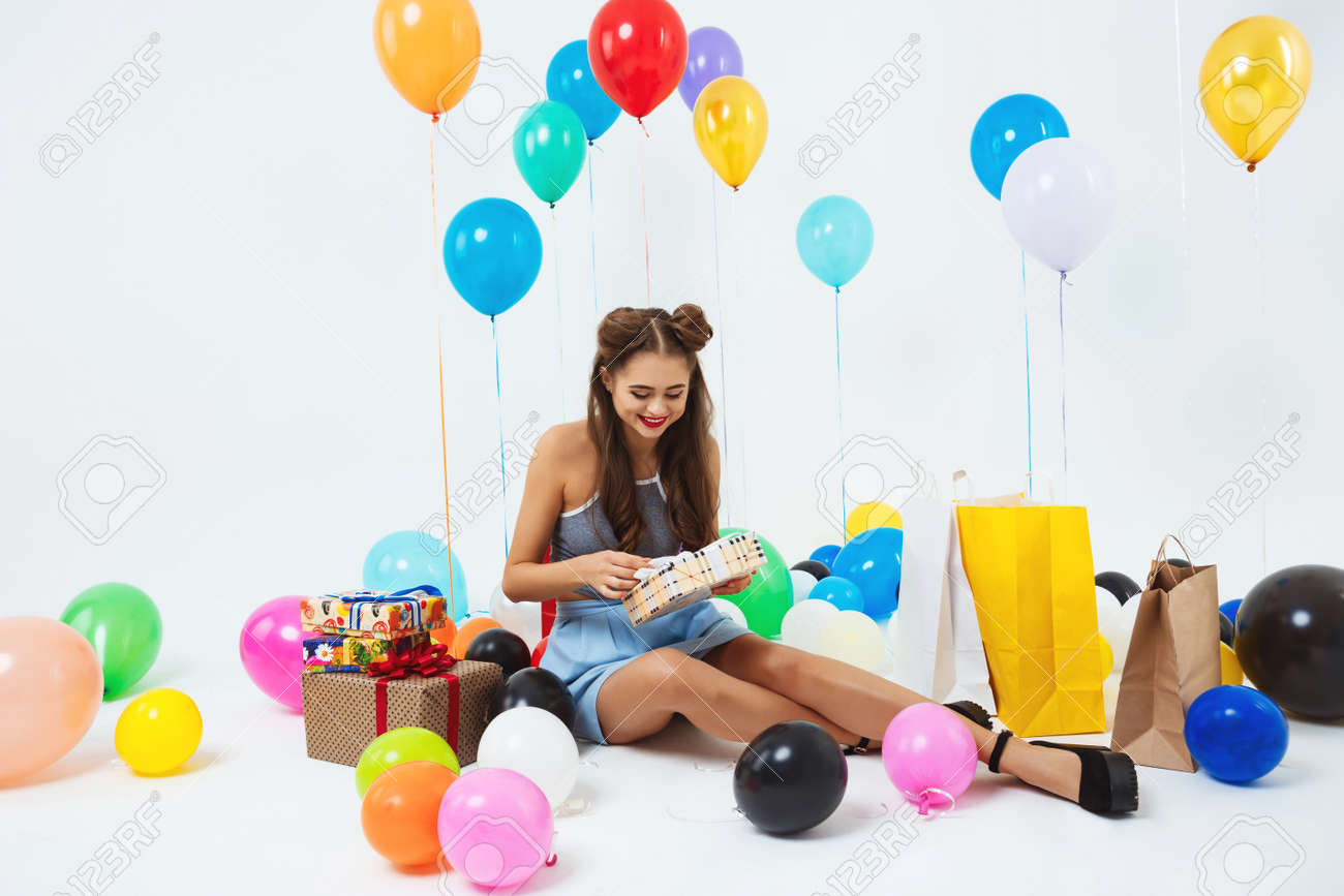glad girl uncovering birthday present boxes sitting with helium