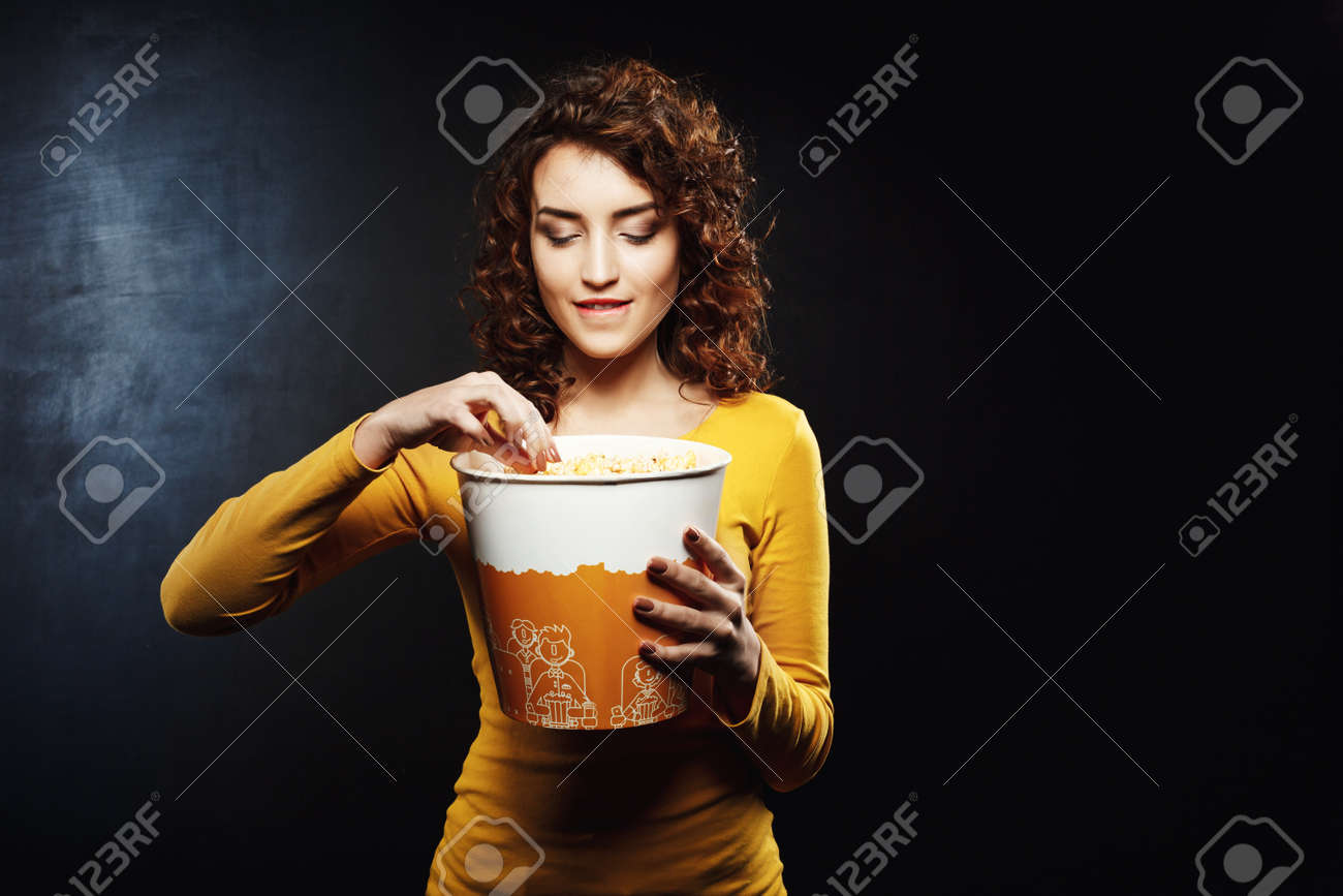 woman with curly hair takes some popcorn biting her underlip stock