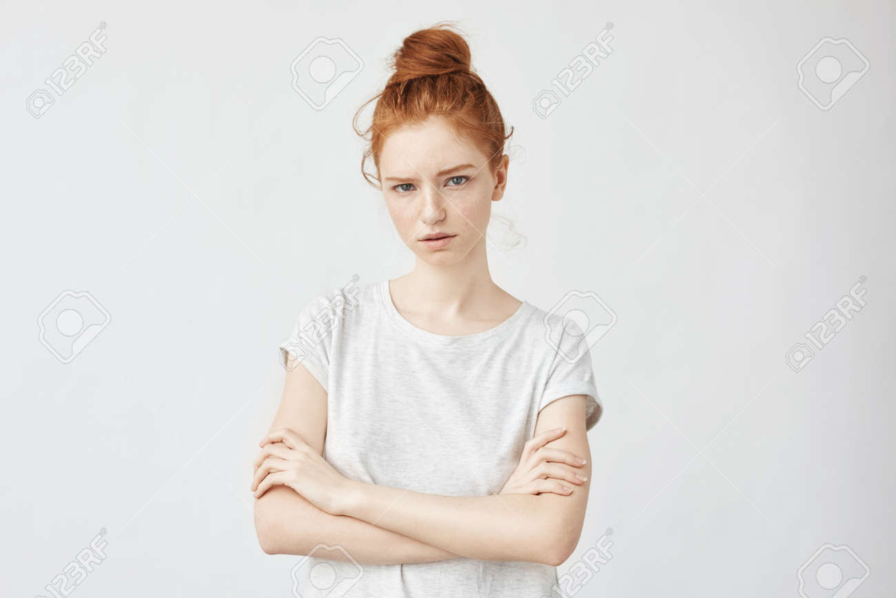 beautiful angry ginger girl looking at camera with crossed arms