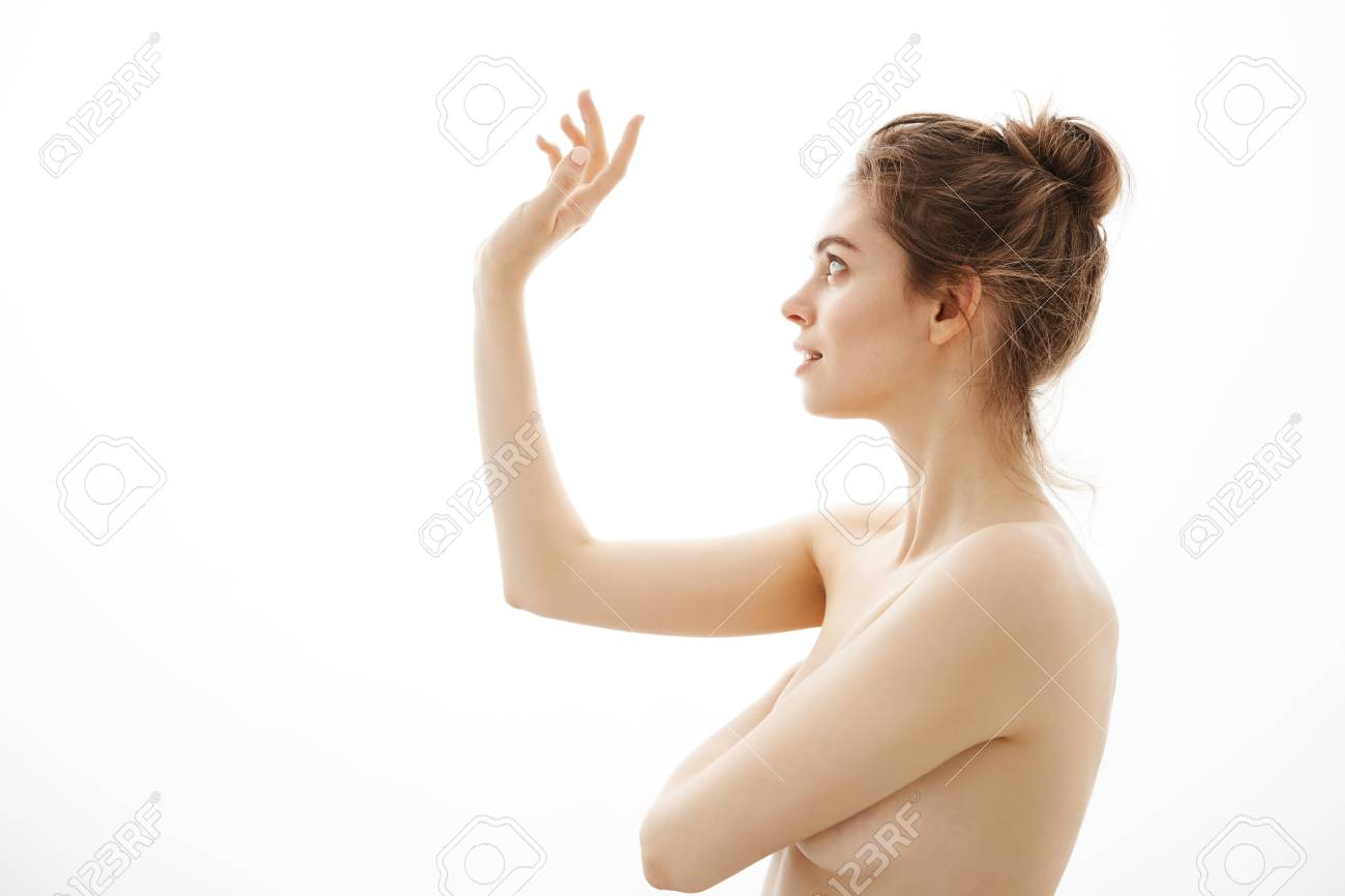 Portrait Of Young Beautiful Tender Naked Girl With Bun Posing In Profile Over White Background