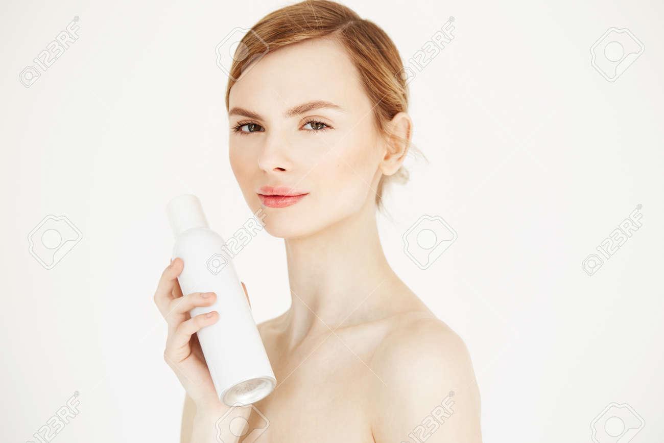 Chica Rubia Hermosa Desnuda Con La Piel Perfecta Sonriente Que Mira La Cámara Mirando La Máscara De La Piel Que Sopla Sobre Fondo Blanco