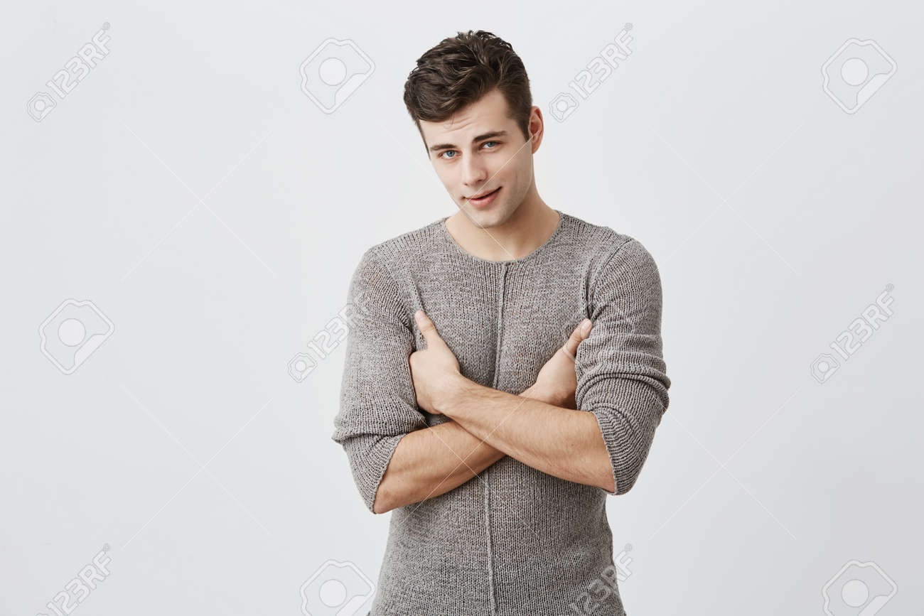 Portrait of serious handsome man with appealing expression, keeps arms folded, tries to be strict. Muscular fit stylish male student being dissatisfied with final mark, demands to retake exam - 90934228