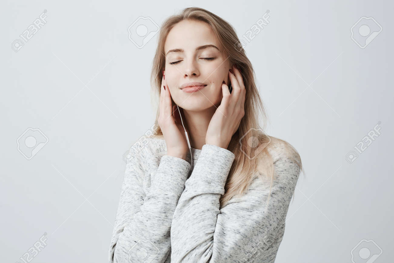 Close-up portrait of beautiful attractive European young woman in gray loose sweater, relaxing with closed eyes, listening to her favourite songs via white earphones, using music app. - 93438342
