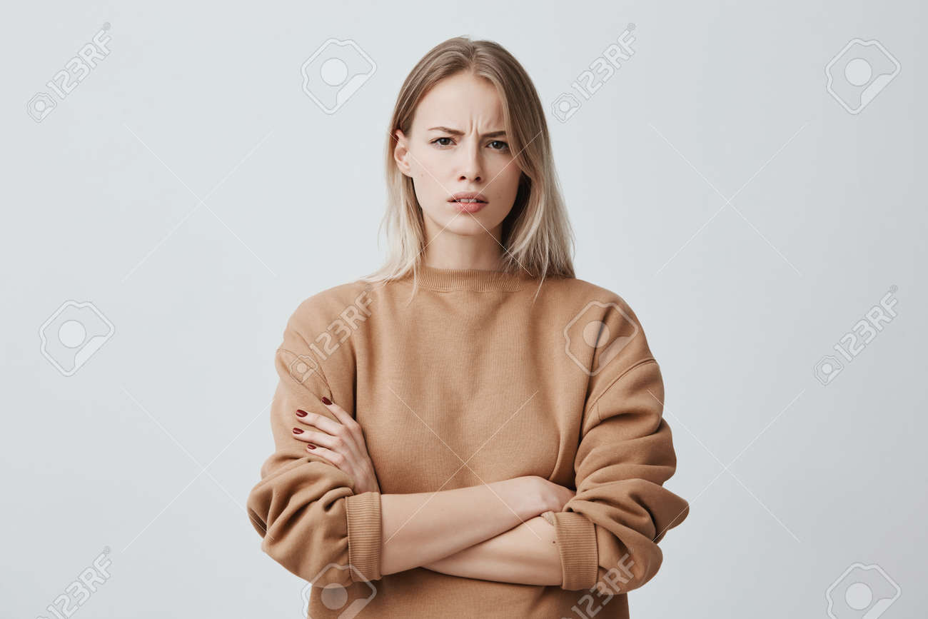 Waist-up portrait of beautiful girl with blonde straight hair frowning her face in displeasure, wearing loose long-sleeved sweater, keeping arms folded. Attractive young woman in closed posture. - 93873312