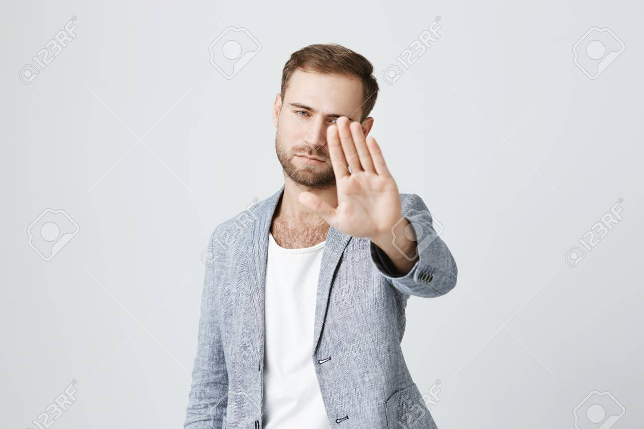 Serious confident angry european man with beard wearing stylish clothes posing against gray studio wall, keeping hands in stop gesture, as if saying: Stay away from me. Body language. - 93879157