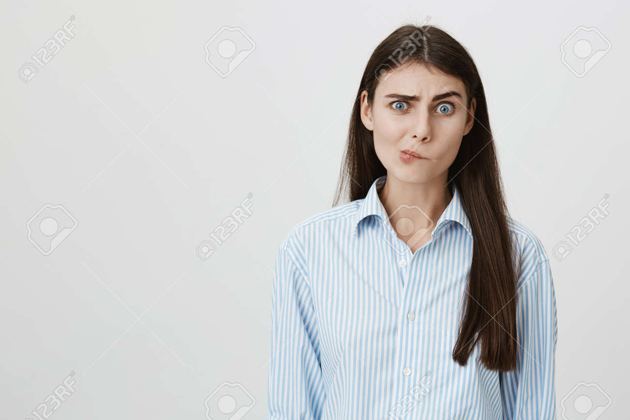 Perplexed and confused woman with questioned expression standing over gray background having no clue what to do next. Foreigner asking her something but she can not understand his language - 95351582
