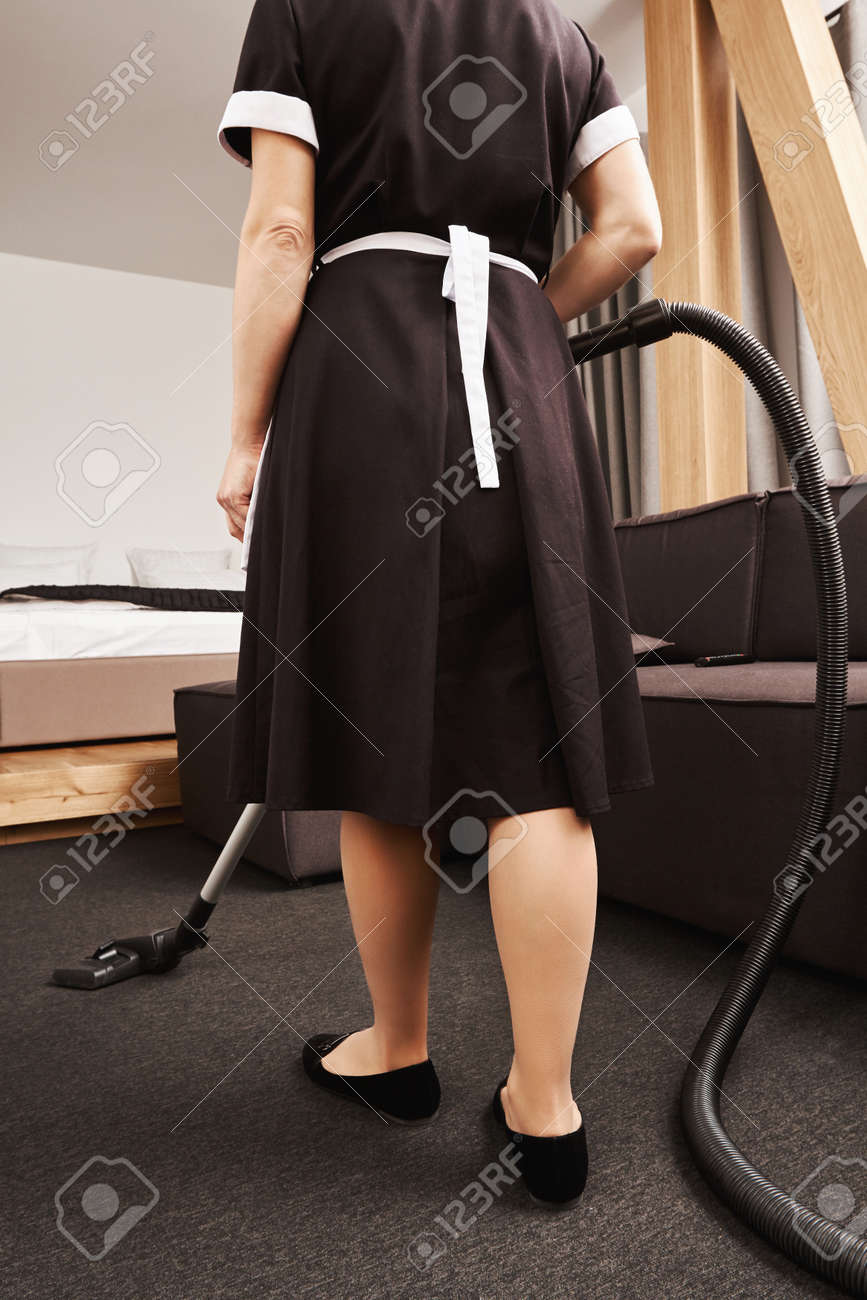 Horizontal Rearview Of Maid In Classic Uniform Cleaning Apartment ...