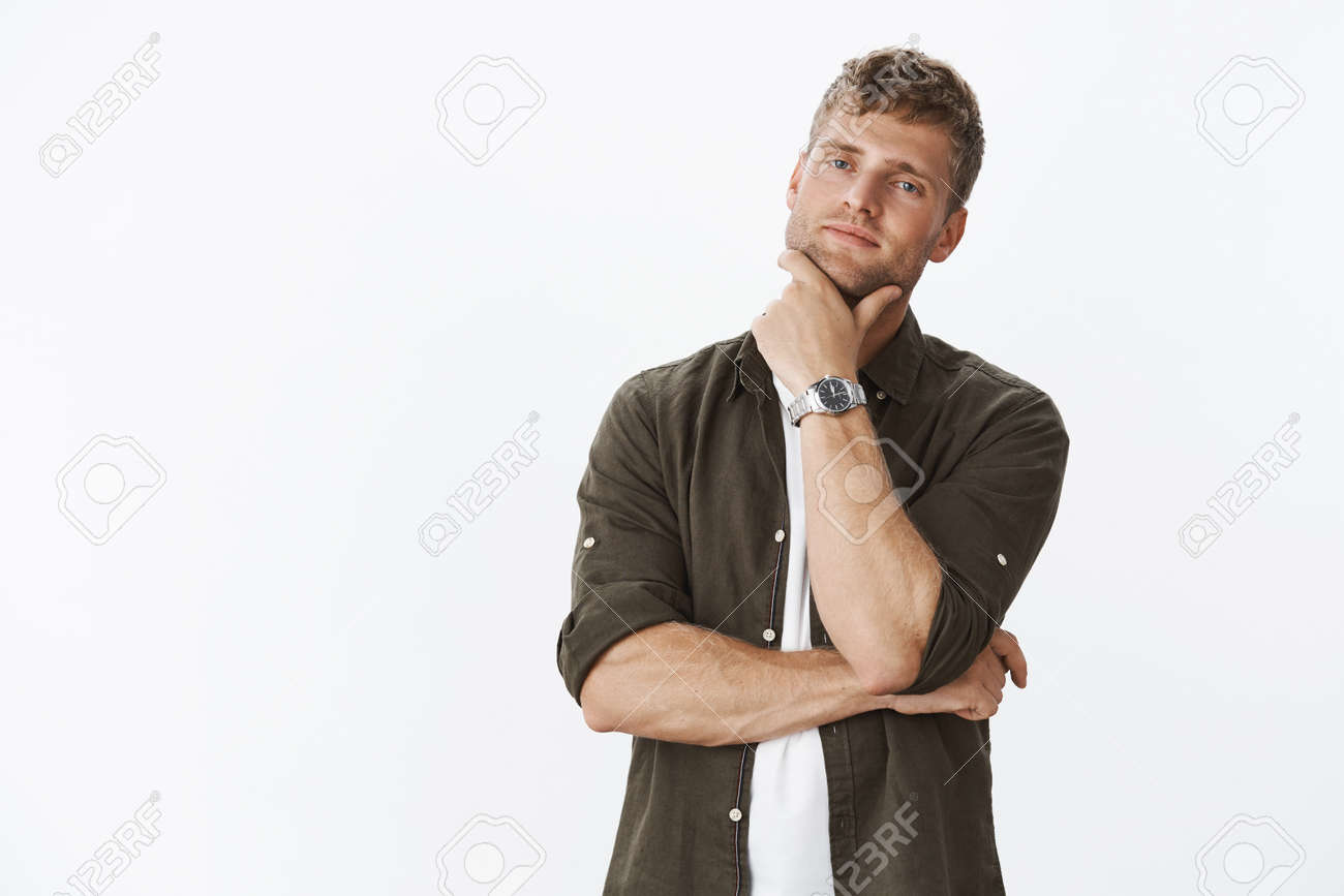 Bossy good-looking smart and confident attractive blond businessman with bristle and watch touching jaw looking determined and curious at camera, thinking, making choice as intrigued with product - 122582939