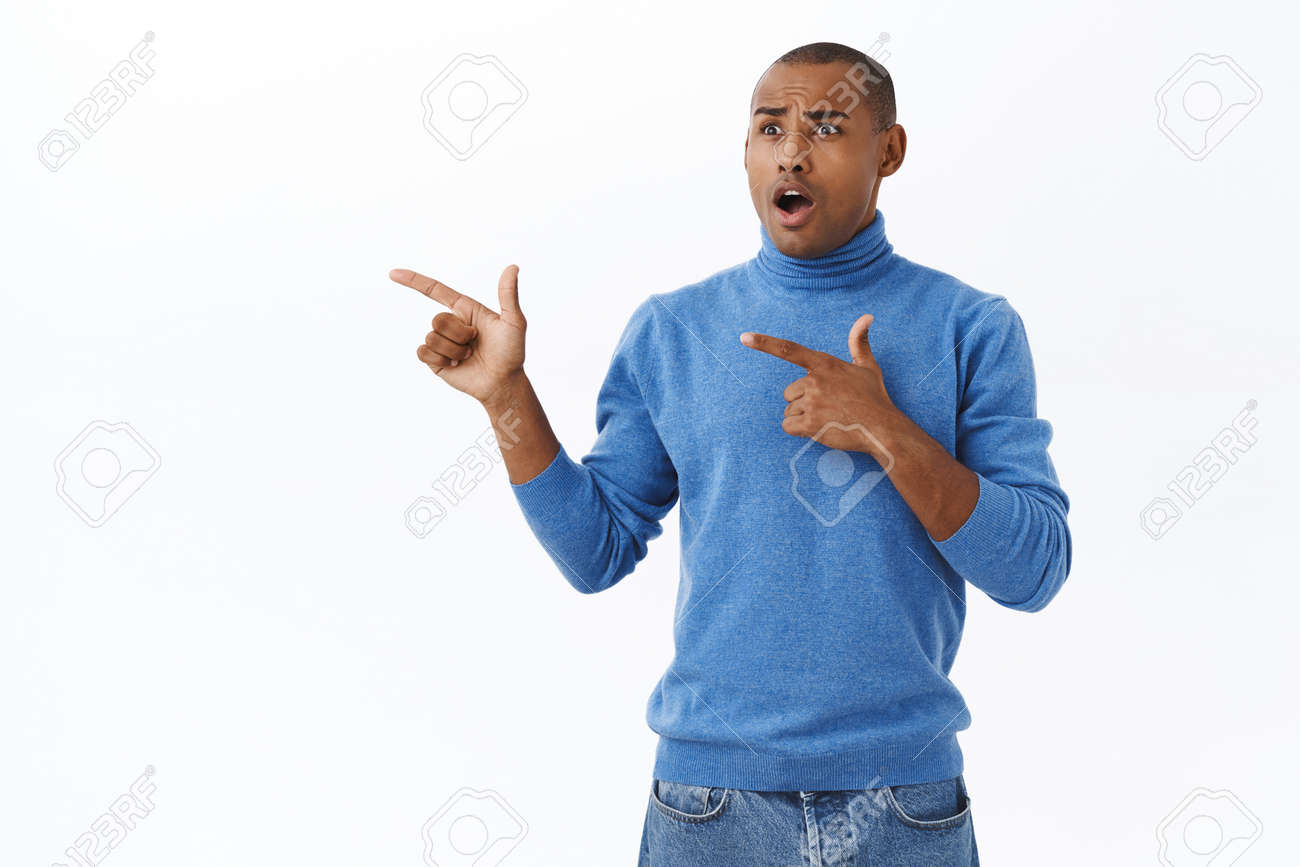 Portrait of shocked, speechless african-american male in turtleneck, pointing fingers left, drop jaw, gasping concerned and astonished, startled over shook news, white background - 143417295