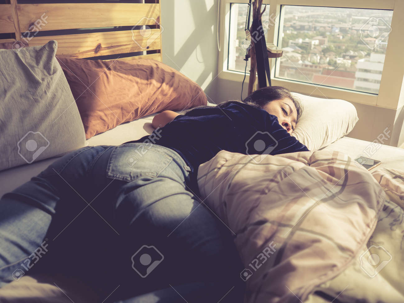 Asian woman sleep on bed in the afternoon. Funny sleeping pose. Stock Photo -